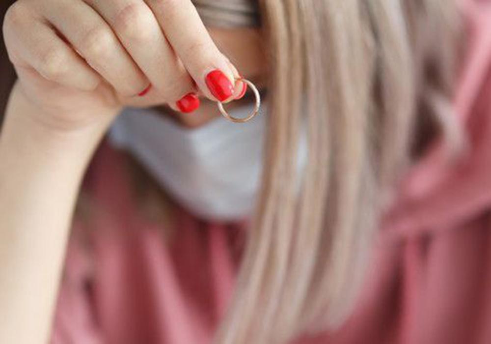 結婚指輪を持って悩んでいるマスク姿の女性