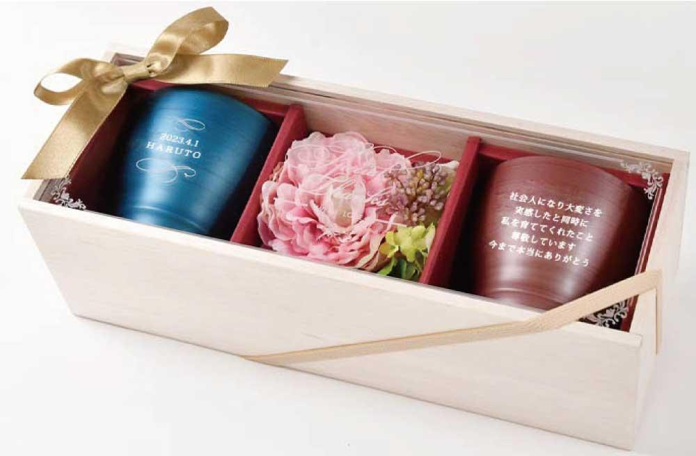 ブルーとワイン色のフリーカップとお花のアレンジが入ったメッセージ刻印入りボックスに入ったペアコップのギフト