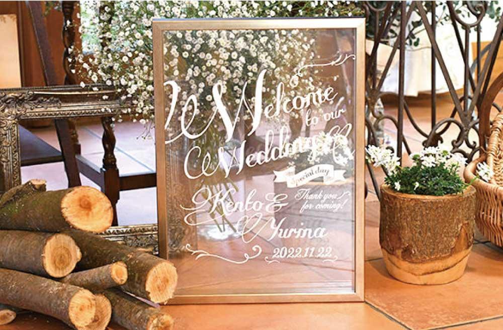 クリアなガラス面に白い時で文字が入ったゴールドのフレームの結婚式用ウェルカムボード