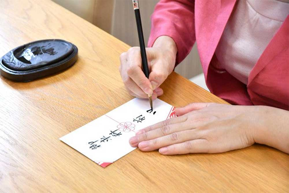 御車料封筒の表書きを筆で描く女性