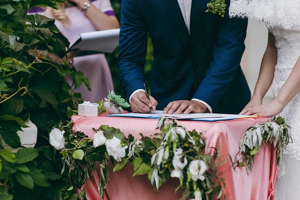 結婚証明書にサインする新郎新婦