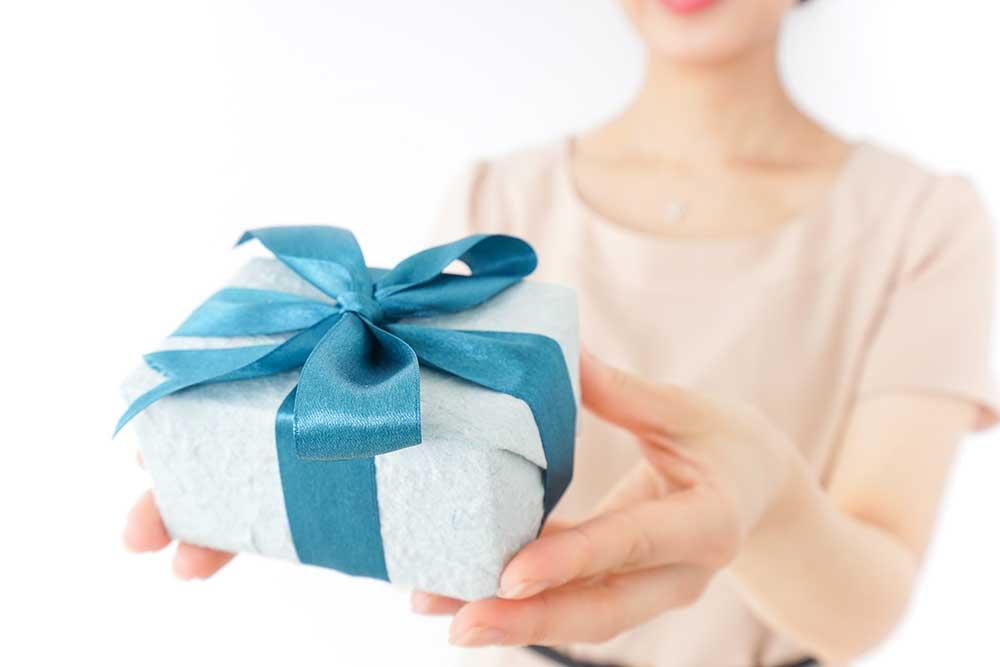 ブルーのリボンをかけたプレゼントを手渡す女性