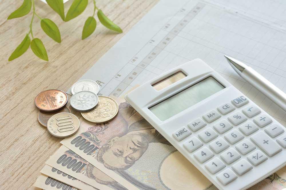 机の上に置かれた紙幣とコインと電卓