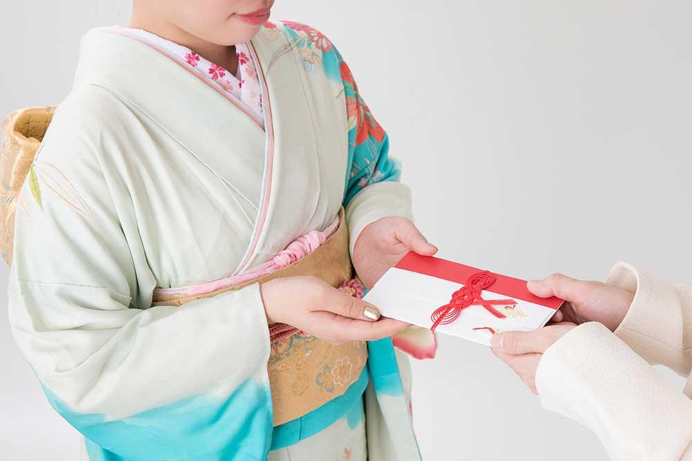 ご祝儀袋を和服姿の女性に手渡す
