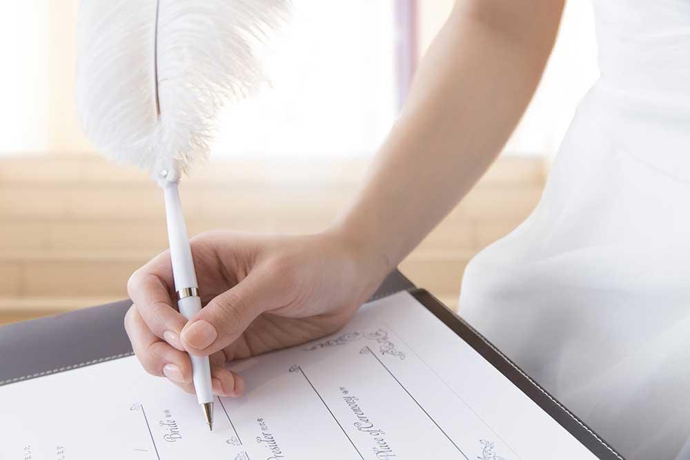結婚証明書に羽根ペンでサインする女性の手元
