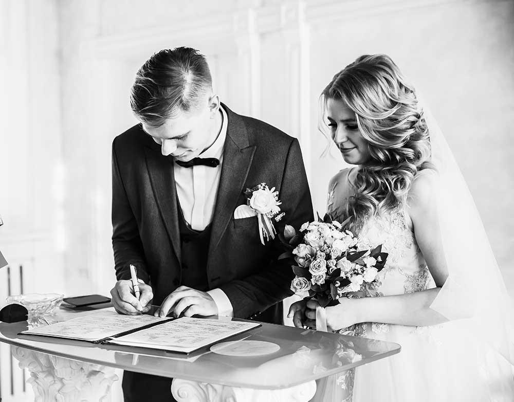 結婚証明書にサインする新郎新婦白黒写真