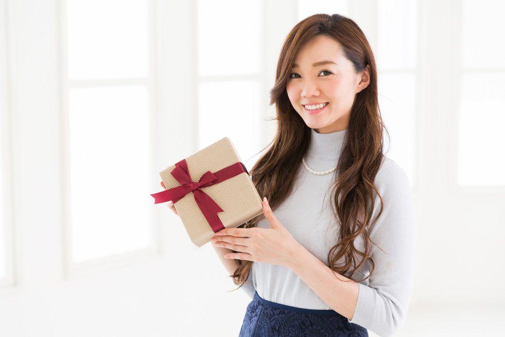プレゼントを持って笑顔の女性