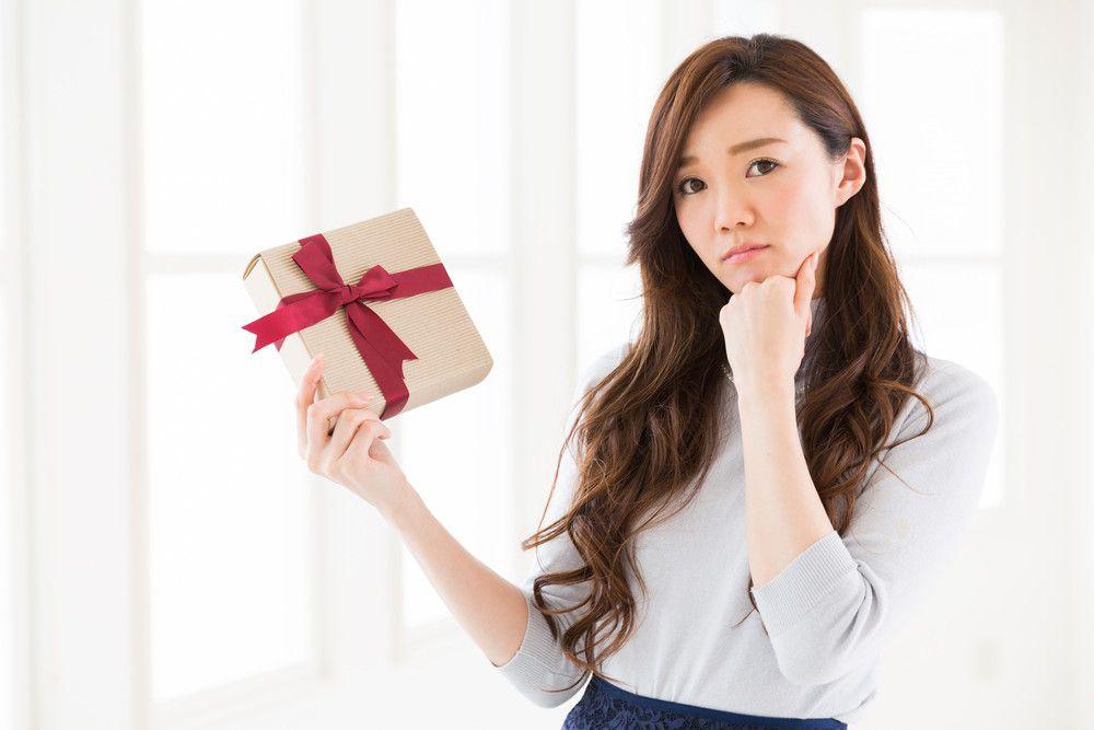 プレゼントを持って悩む女性
