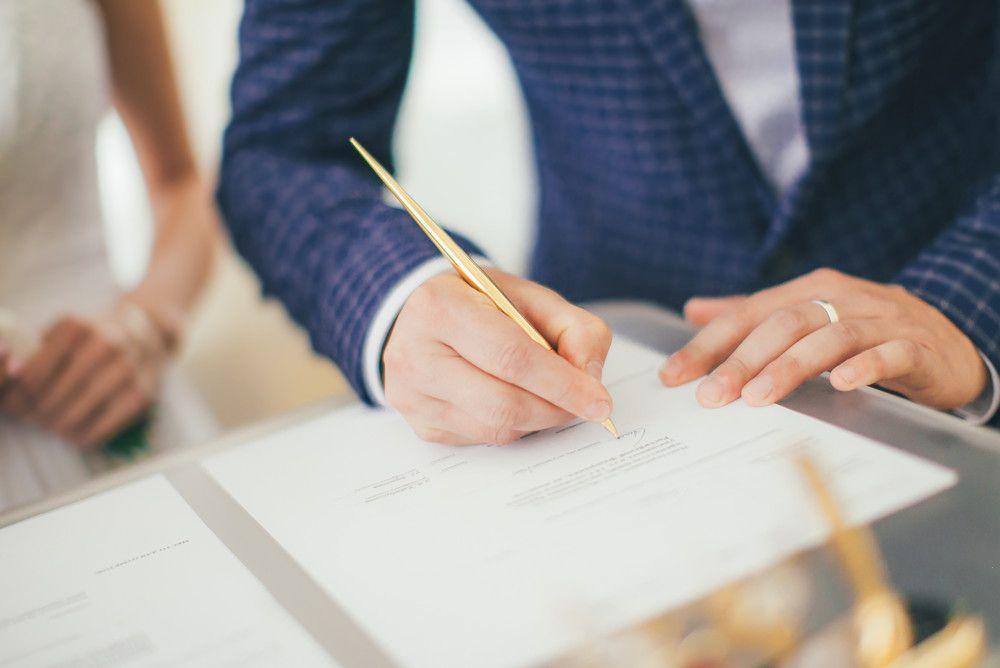 結婚証明書にサインする新郎