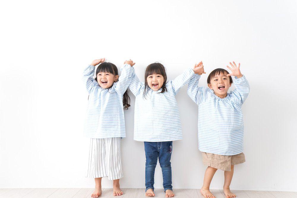 幼稚園児3人が楽しく両手をあげている
