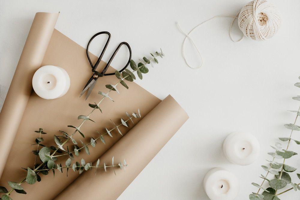 ユーカリの葉っぱやクラフト梱包材、紐、ハサミなどが机に置かれている