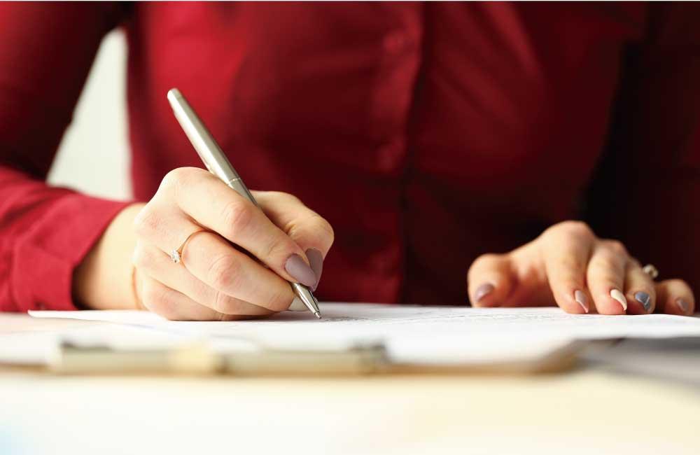 文字をペンで書く女性