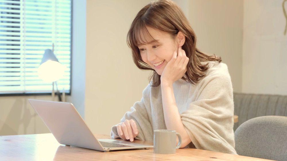 パソコンを見ながら微笑む女性
