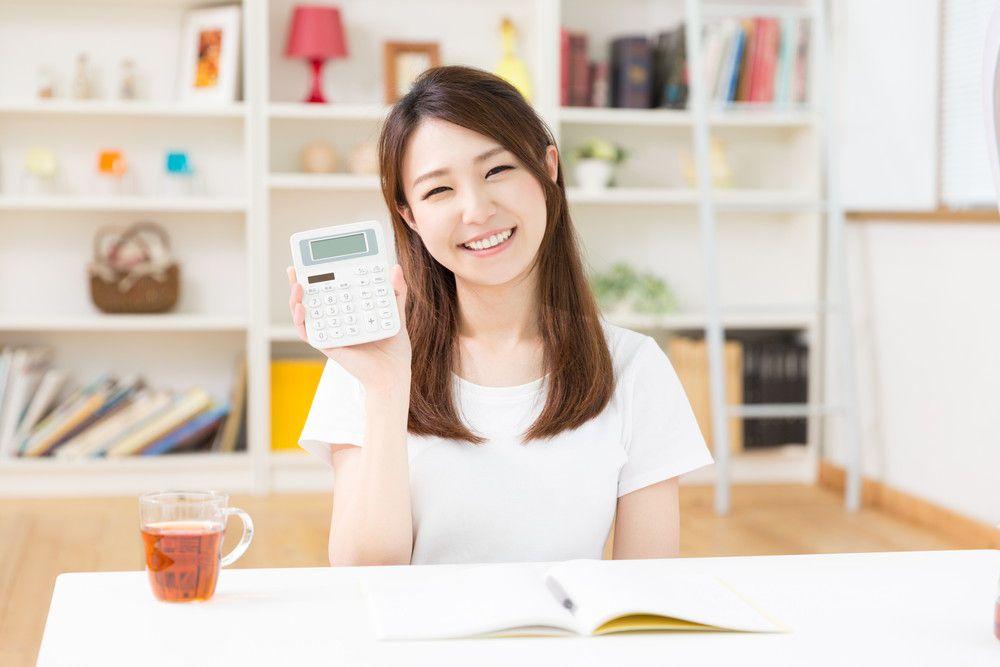 計算機を片手に見せながら笑顔の女性