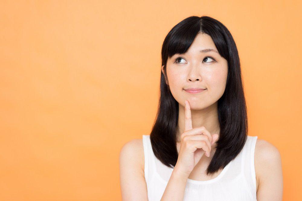 人差し指を顎に置きながら考える女性