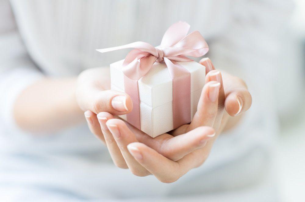 ピンクのリボンを付けたプレゼントを両手で持っている