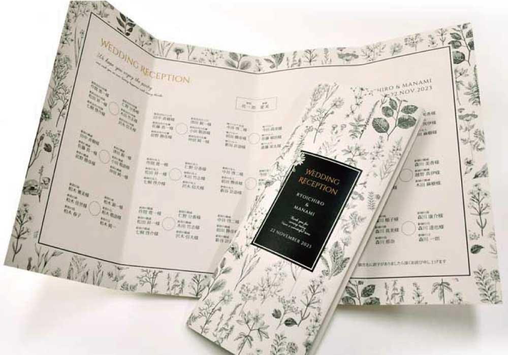 アッシュグレーのペーパーにボタニカルフラワー柄が黒で印刷されたスタイリッシュな席次表
